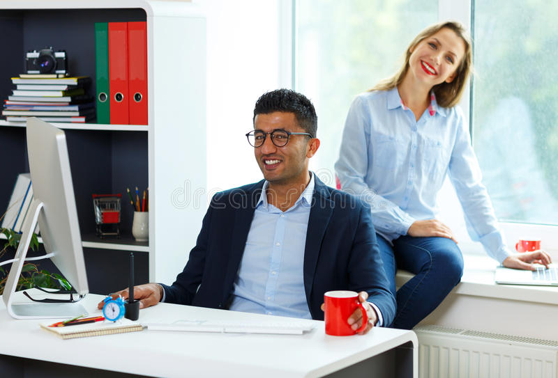Beautiful young woman and man working from home office. Beautiful young women and men working from home office - modern business concept royalty free stock photography