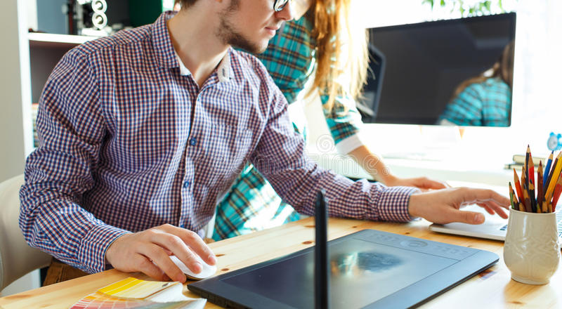 Beautiful young woman and man working from home office. Beautiful young women and men working from home office - modern business concept royalty free stock image