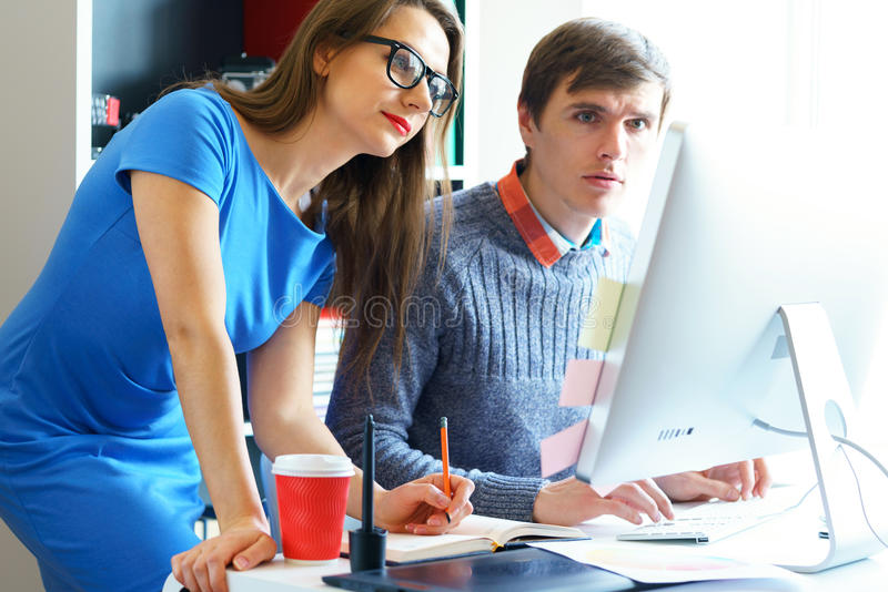 Beautiful young woman and man working from home office. Beautiful young women and men working from home office - modern business concept royalty free stock photo