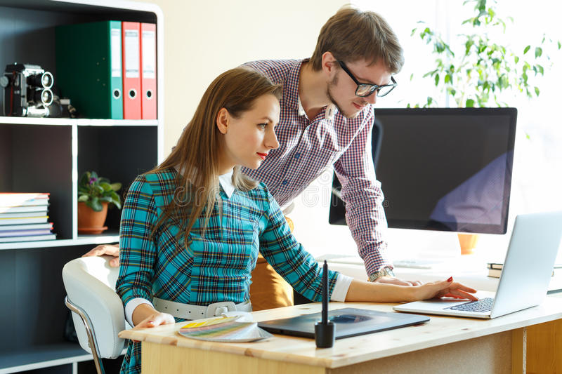 Beautiful young woman and man working from home. Beautiful young women and men working from home - modern business concept royalty free stock photography