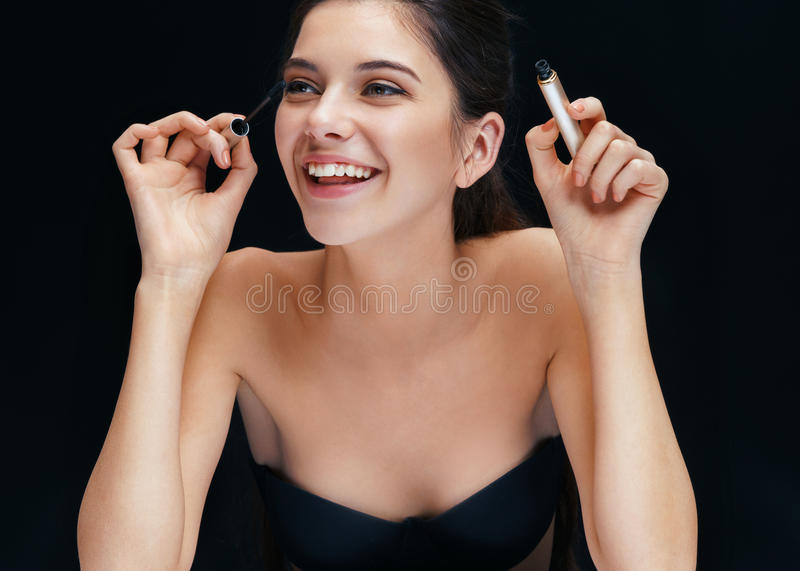 Beautiful young woman with mascara brush. Photo of smiling brunette girl on black background royalty free stock photography
