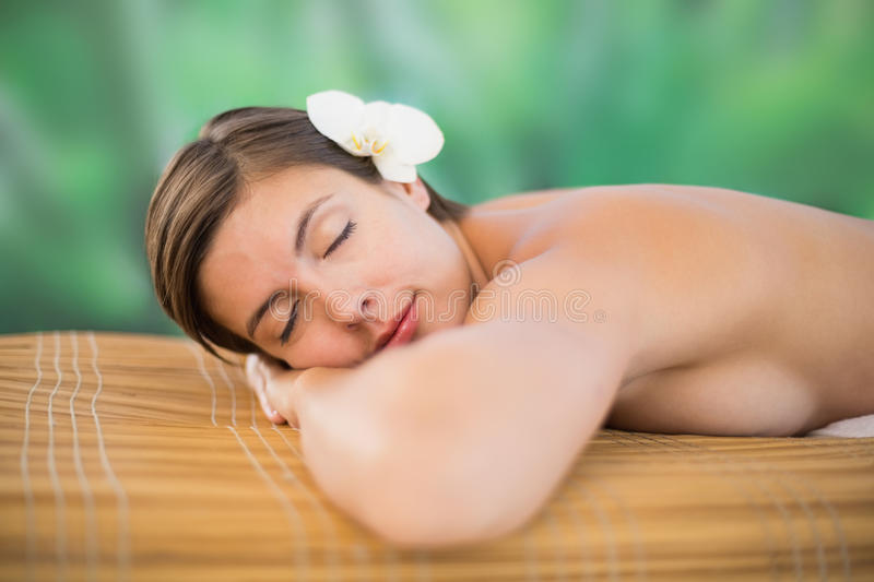 Beautiful young woman on massage table. Side view of a beautiful young woman on massage table at health farm royalty free stock images