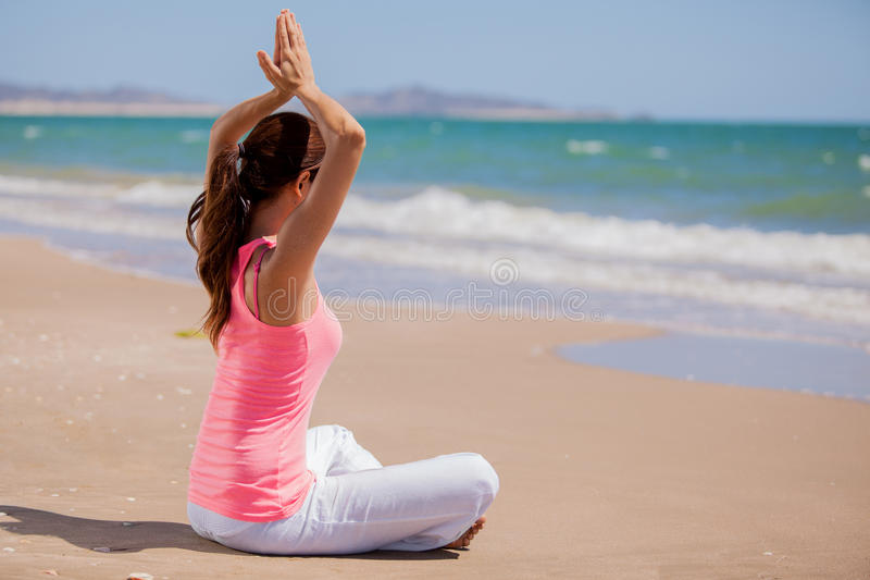 Beautiful young woman meditating. Cute young woman doing some meditation and yoga at the beach on a sunny day royalty free stock photos