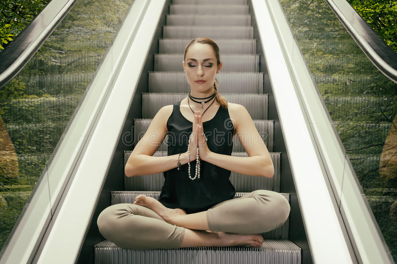 Beautiful Young Woman Meditating on the Escalator with Forest Background, Sitting in Yoga Lotus Posture with Closed Eyes. Str stock photo