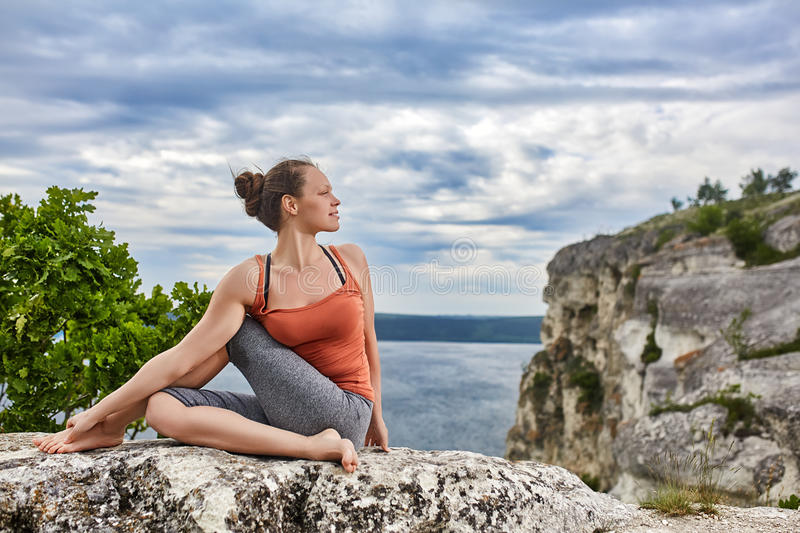 Beautiful young woman meditating in yoga pose at a big river against dramatic sky. stock photography