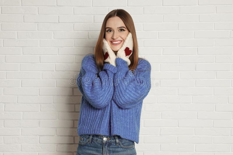 Beautiful young woman in mittens and blue sweater near white brick wall stock photography