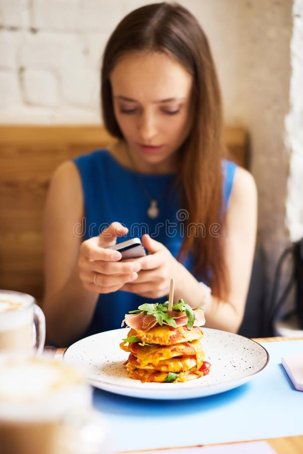Beautiful young woman with mobile phone eating tasty pancake in cafe stock photos