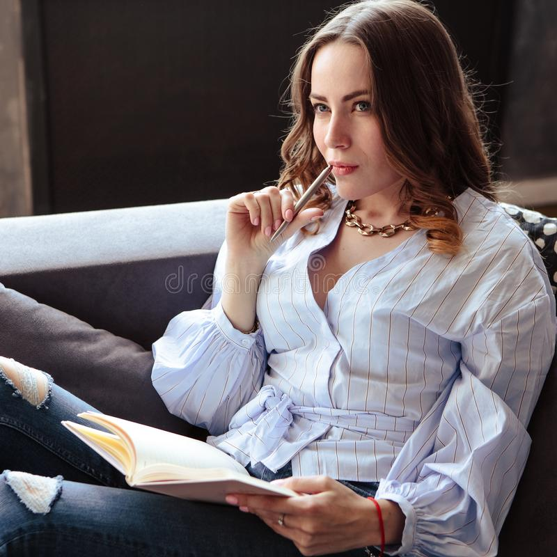 Beautiful young woman with mobile phone schedule notebook in stylish home interior. Freelancer in her working place. royalty free stock photography