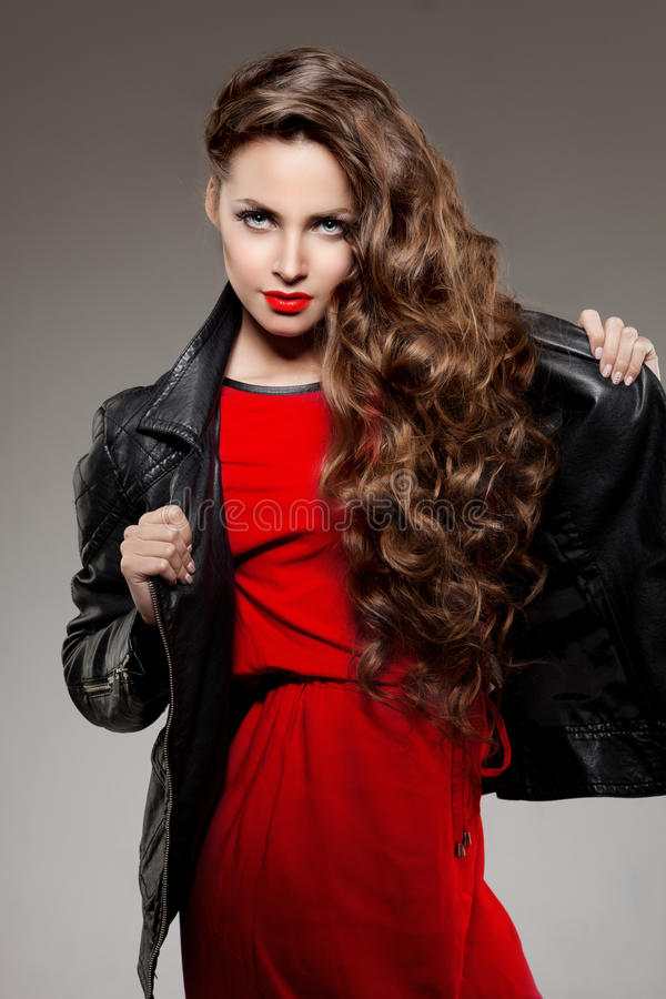 Beautiful young woman model brunette with long curled hair with. Red lips in leather jacket. Girl wave, curly hairstyle. Health hair shine. Beauty lady face stock photo