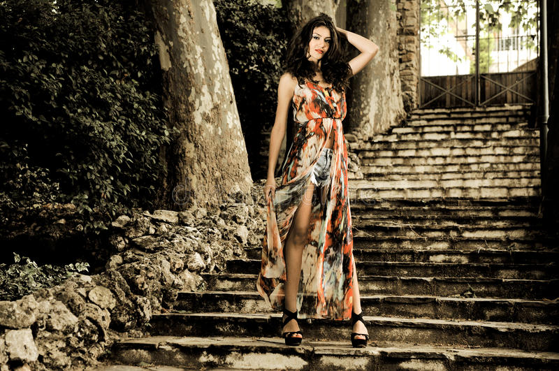 Beautiful young woman, model of fashion, in a garden stairs royalty free stock images