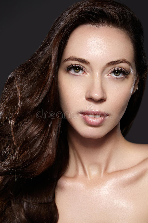 Beautiful young woman model with flying brown color hair. . Make up, curly hairstyle. Haircare, make-up. Beautiful young woman model with flying brown color royalty free stock photo