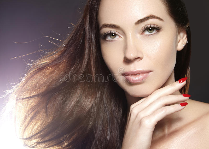 Beautiful young woman model with flying brown color hair. . Make up, curly hairstyle. Haircare, make-up. Beautiful young woman model with flying brown color royalty free stock image