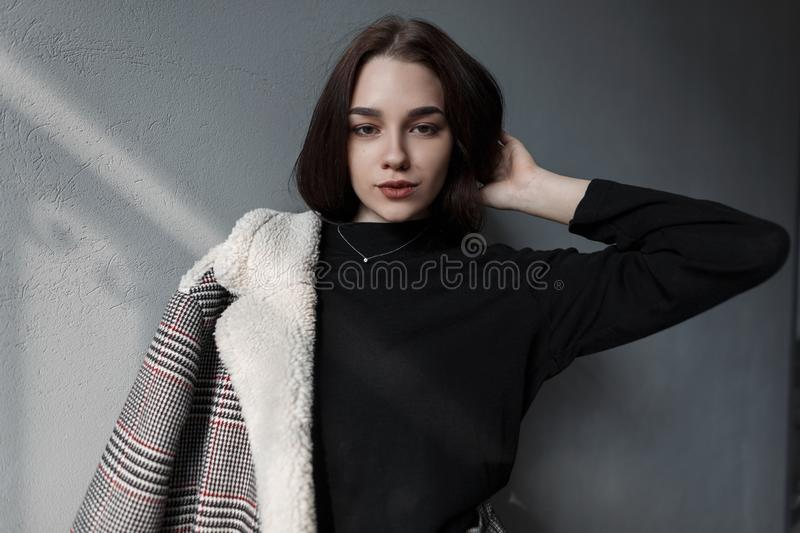 Beautiful young woman model with natural make-up with beautiful eyes in fashionable spring clothes is resting standing. Near the gray concrete wall in the room royalty free stock image