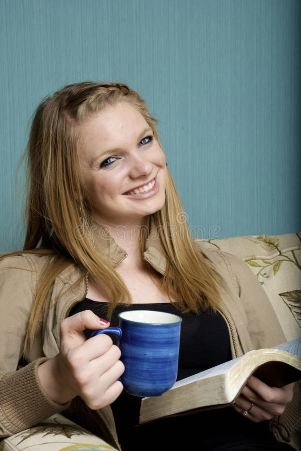 Beautiful Young Woman with morning coffee and bibl. E on a blue background royalty free stock images
