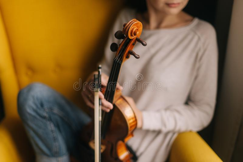 Beautiful young woman musician posing with a violin in a soft chair royalty free stock photos