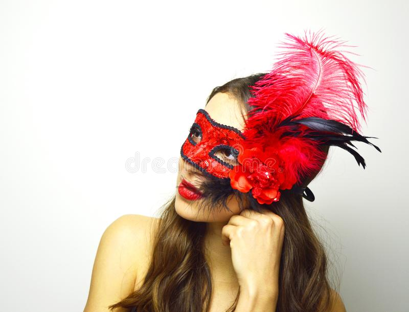 Beautiful young woman in mysterious Venetian mask. girl with red flower carnival mask. Attractive female ready for carnival. royalty free stock photography