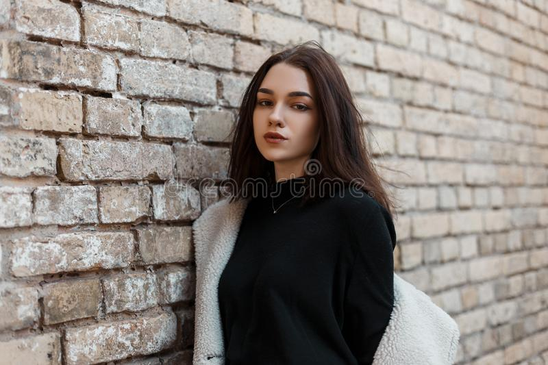 Beautiful young woman with natural make-up with beautiful eyes in fashionable spring clothes is resting standing. Near an old brick building in the city stock images