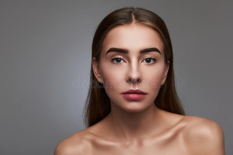 Beautiful young woman with natural make-up posing against gray background royalty free stock photos