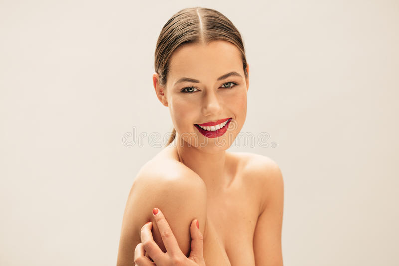 Beautiful young woman with natural makeup. Portrait of beautiful young woman with natural makeup. Pretty female model posing topless and smiling against beige stock photo