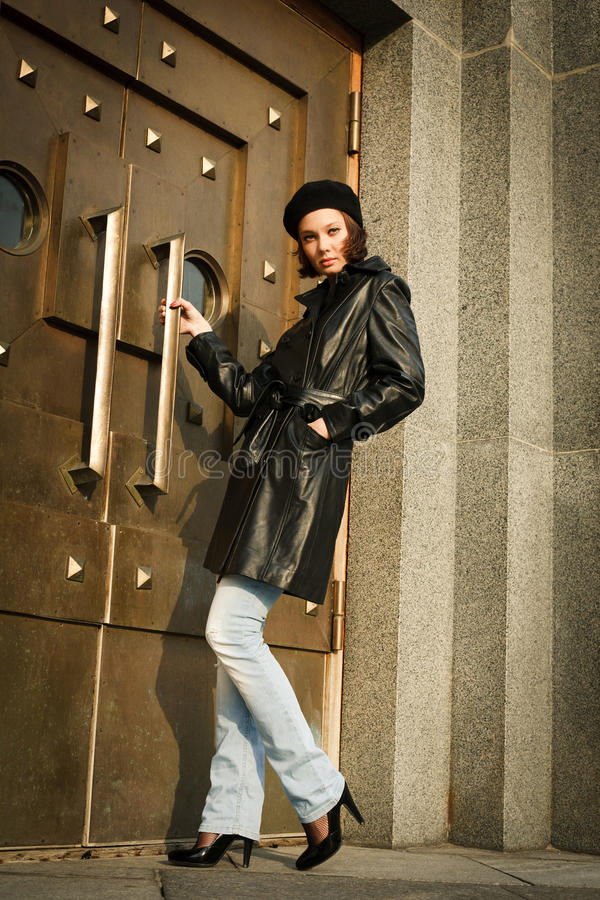 Beautiful young woman near the bronze doors stock images