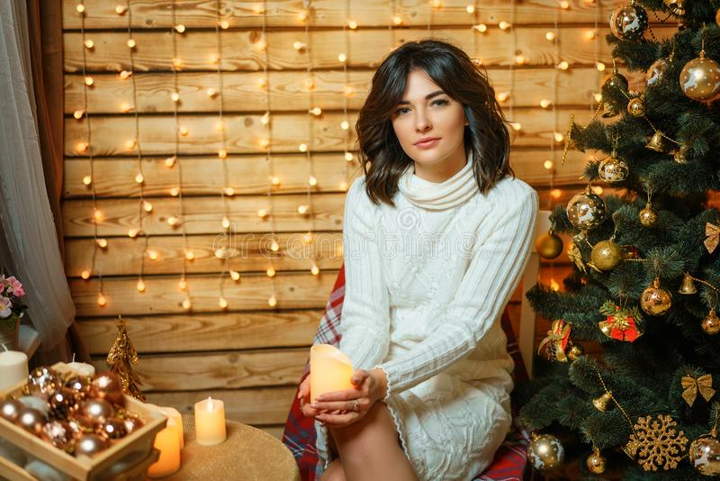 Beautiful young woman near the Christmas tree in a white sweater, cozy waiting for new year and Christmas holidays royalty free stock photography