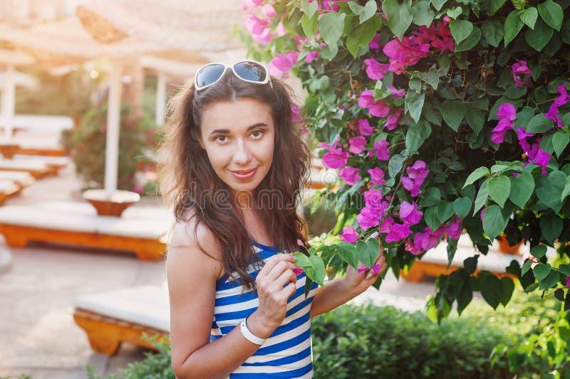 Beautiful young woman near the flowering bougainvillea. Beautiful young woman on vacation near the flowering bougainvillea bush stock images