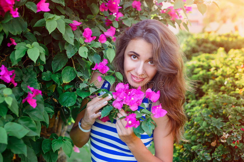 Beautiful young woman near the flowering bougainvillea. Beautiful young woman on vacation near the flowering bougainvillea bush royalty free stock photography