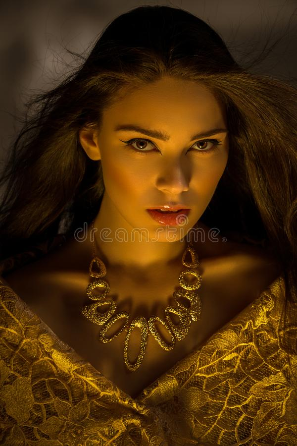 Beautiful young woman with necklace in golden light stock image