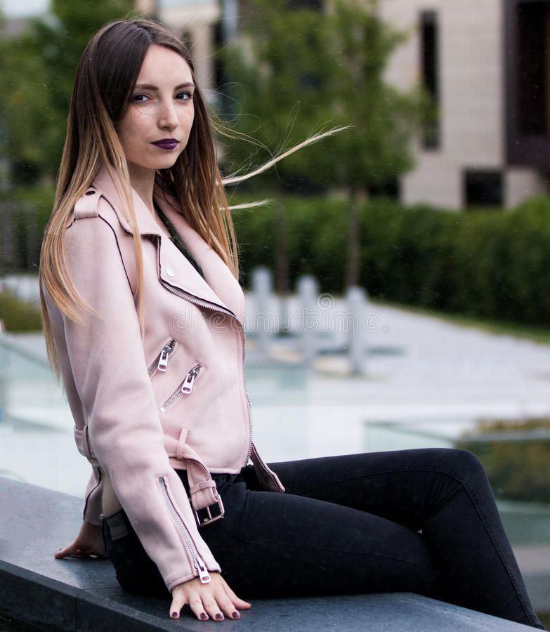 Beautiful young woman next to fountain on street of the city royalty free stock photos