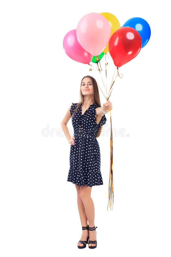 Beautiful young woman offering colorful balloons. Full length portrait of beautiful young woman in polka dot dress offering colorful balloons isolated on white stock photo
