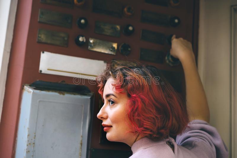 Beautiful young woman with orange hair ringing the door of an apartment royalty free stock photography