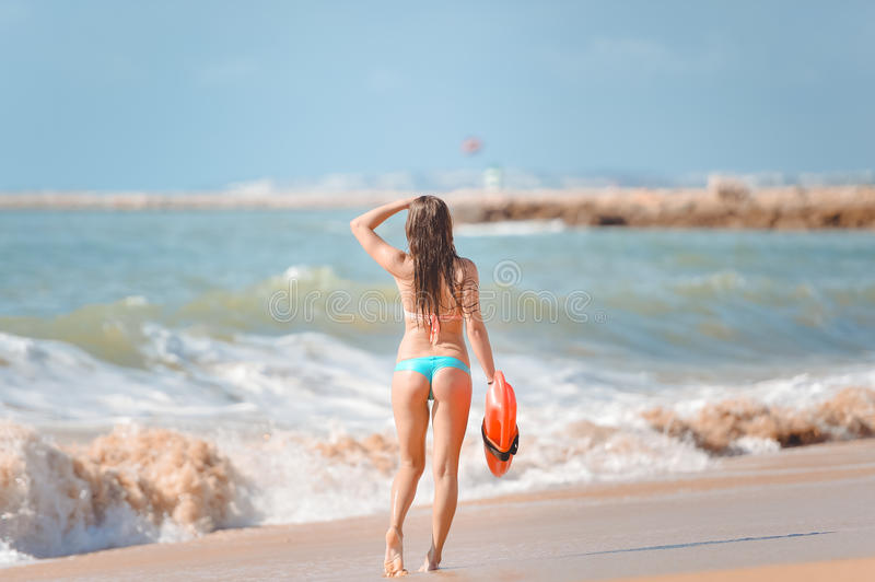 Beautiful young woman with orange lifesaver royalty free stock image