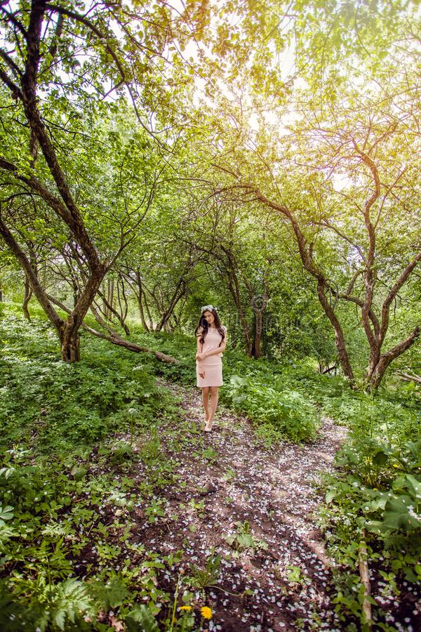 Beautiful young woman outdoors. Beauty girl brunette in white flowers wreath in hair walking in spring blossom garden royalty free stock photography