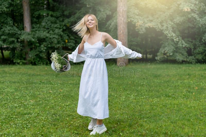 Beautiful Young Woman Outdoors holding basket with daisies. Enjoy Nature. Healthy Smiling Girl in Green Grass. royalty free stock photo