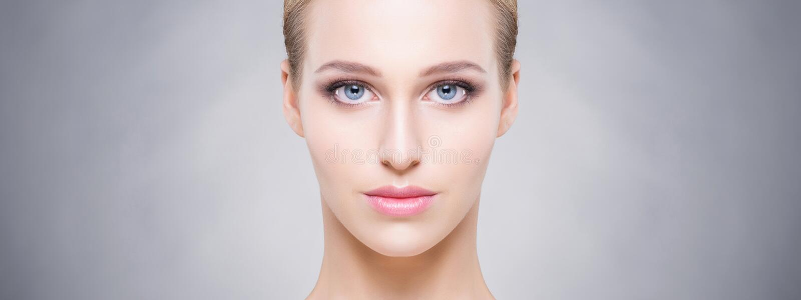 Beautiful and young woman over the grey background. Healthy skin royalty free stock image