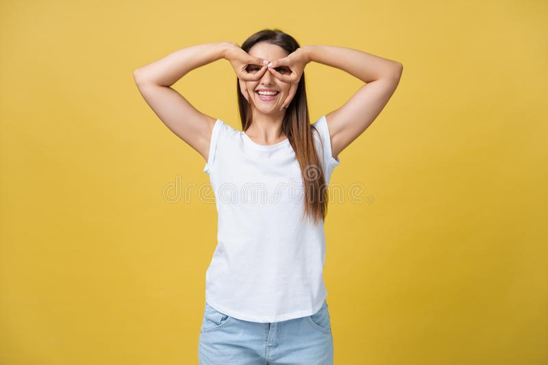 Beautiful young woman over yellow background happy face smiling doing ok or glass sign with hand on eye looking through. Fingers stock images