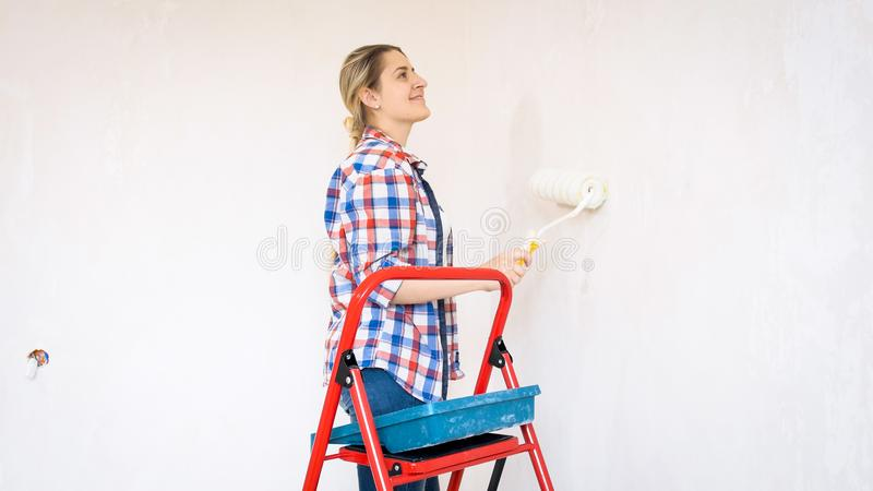 Portrait of beautiful young woman painting walls with paint roller royalty free stock photos