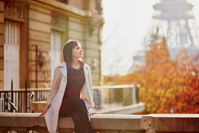 Young woman in Paris near the Eiffel tower on a fall day stock photo
