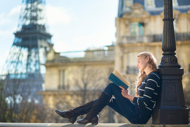 Beautiful young woman in Paris, reading a book. Near the Eiffel tower royalty free stock images