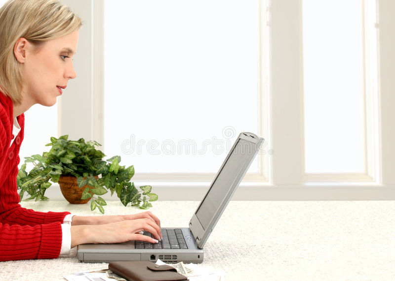 Beautiful Young Woman Paying Bills Online. Version with houseplant. Casual woman in red sweater paying bills online at home. Space for copy to right royalty free stock photography