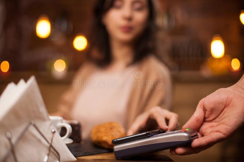 Beautiful young woman paying coffee using NFC technology in a coffee shop royalty free stock photo