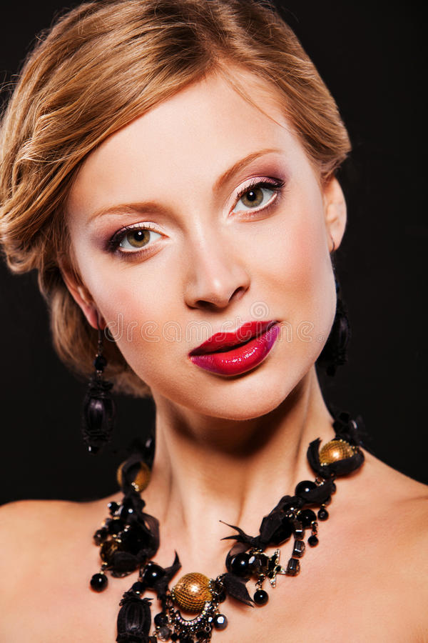 Beautiful young woman with perfect evening makeup wearing jewelry royalty free stock image