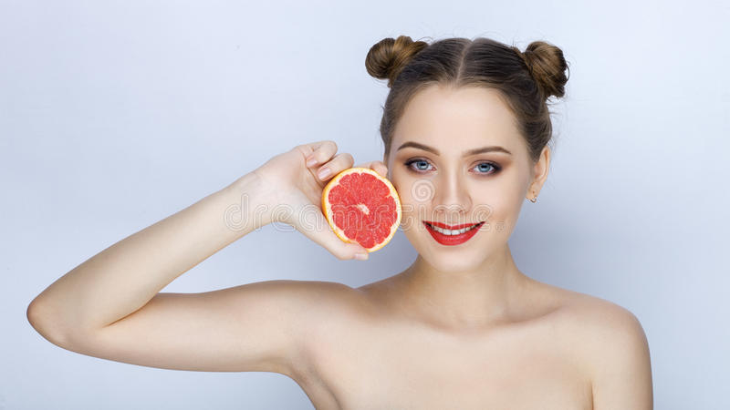 Beautiful young woman with perfect healthy skin funny hairdo trendy makeup bare shoulders holding grapefruit healthy eating. Beautiful young lady with perfect royalty free stock photography