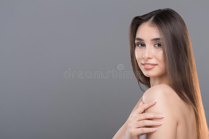 Beautiful young woman with perfect skin and hair. Health and beauty. Beautiful young woman with perfect skin and hair, grey panorama background with empty space royalty free stock photos