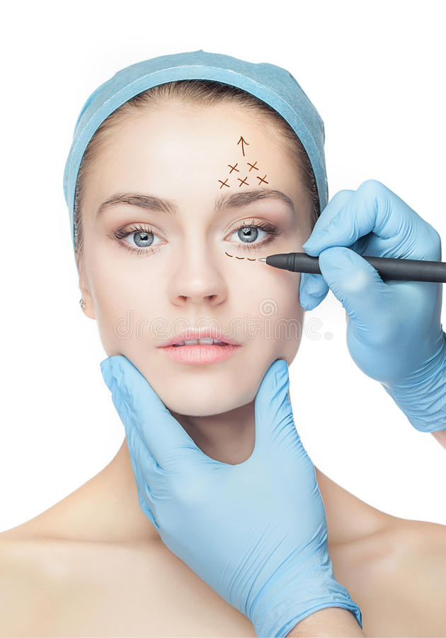 Beautiful young woman with perforation lines on her face before plastic surgery operation. royalty free stock photo