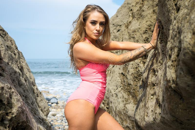 Beautiful young woman in pink bathing suit stood between the rocks royalty free stock photo