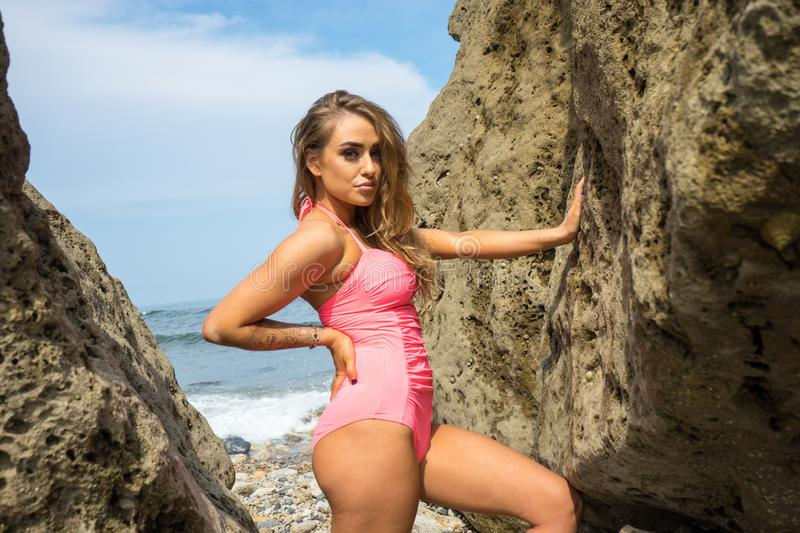 Beautiful young woman in pink bathing suit stood between the rocks royalty free stock photography