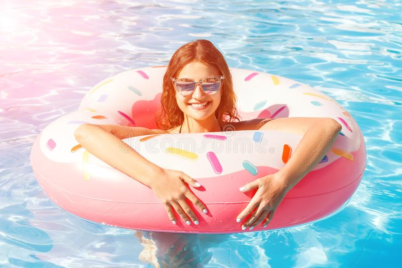Beautiful young woman with pink circle relaxing in blue swimming pool stock image