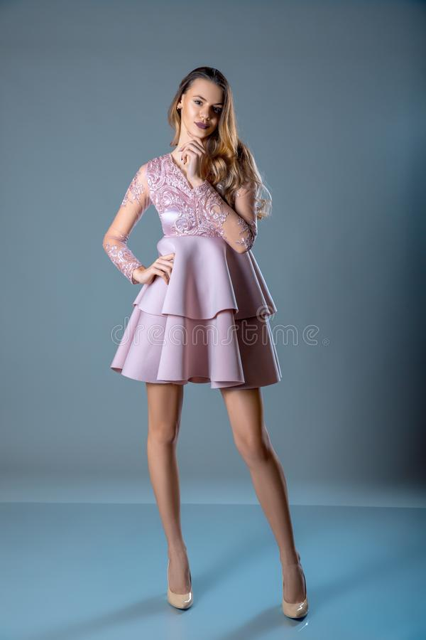 Beautiful young woman in a pink dress with frills, stands on a blue gray background stock images