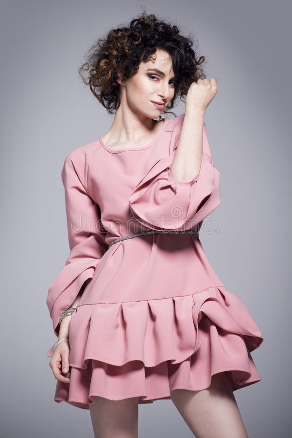 Beautiful young woman in a pink dress with frills stock image